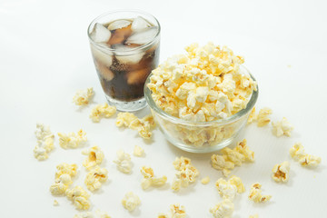 Glass bowl with popcorn on white background