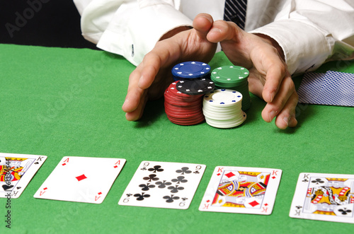 Hands in foreground betting poker