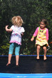 Happy children jumping on trampoline