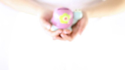 Hands showing small smiling turtle piggy bank