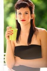 Beautiful Girl Drinking Tea Coffee Indoor. Green Background