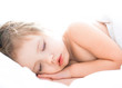 Cute baby girl is sleeping on white bed
