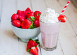 Leinwandbild Motiv Strawberry milkshake on wooden background