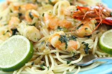 spaghetti with fried shrimps and some drops of lime