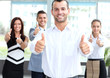 attractive businessman with team in office showing thumbs up