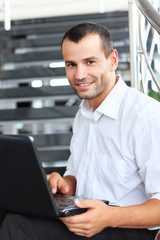 Businessman sitting on stairs and using laptop pc.