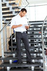 Portrait of positive business man standing on stairs