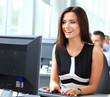 Casual businesswoman using laptop in office, sitting at desk