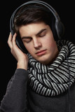Уoung man listening to music on headphones