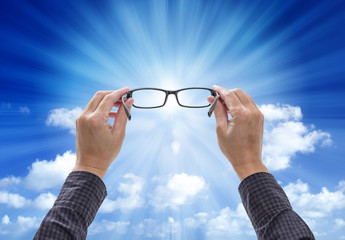 Hands holding eyeglasses isolated on blue sky background