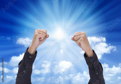 Man hand with a fist, isolated on blue sky background