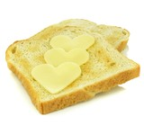 Toast with heart shaped cheese slices on white background