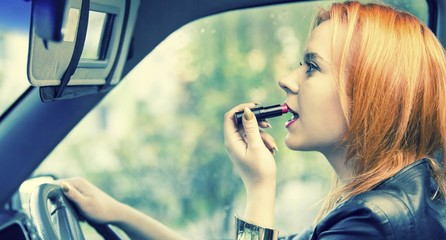 Woman applying lipstick on lips in car. Danger on road.