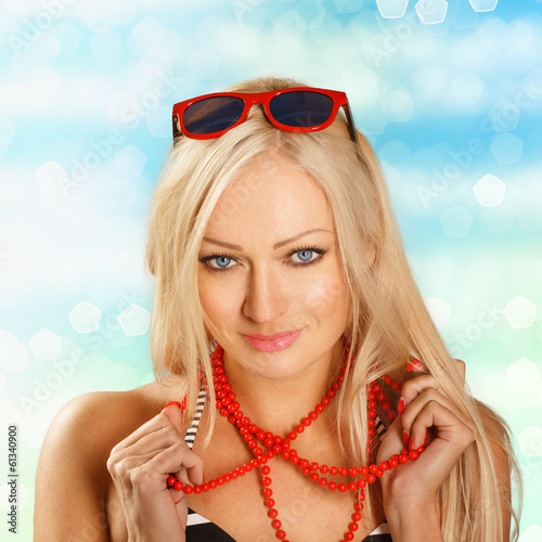 Sexy bikini woman on the seaside holding her red beads. Shining