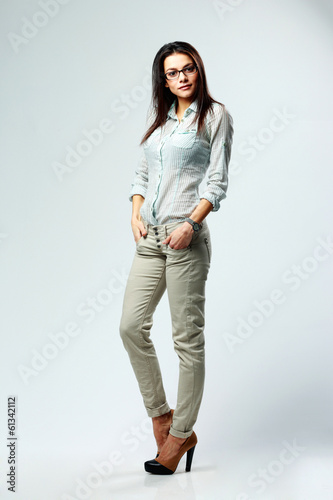 beautiful businesswoman standing on gray background