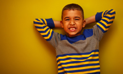 Afro American boy against yellow background