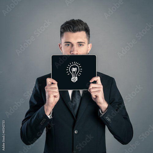 Young businessman portrait having an idea against dark backgroun
