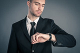 Businessman looking at the time on his wrist watch against dark