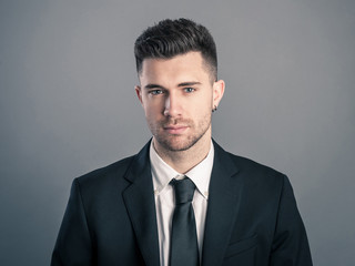 Young businessman portrait against dark background.