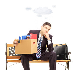 Sad young businessman with cloud over head holding box