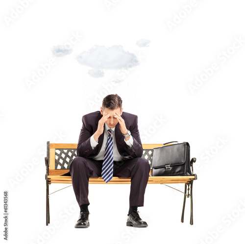 Worried young businessman sitting on bench with cloud over head