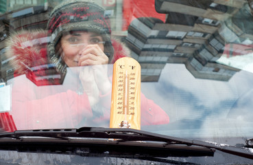 Girl inside the car with a thermometer on the wind screen