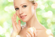 beauty woman with cream and  natural skin care in green