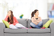 Two angry teenage girls sitting on sofa, at home,