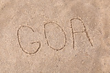 Inscription Goa in wet sand close-up background