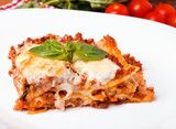 Tasty lasagna on white plate close-up