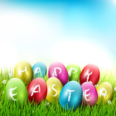 Happy Easter - colorful eggs lying in the grass