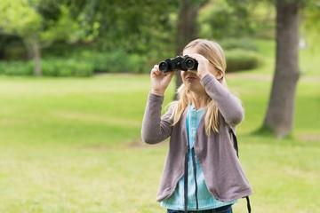 Young girl looking through binoculars at park