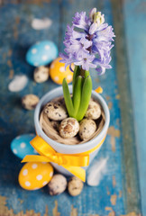 Easter still life with a blue flower on a wooden background