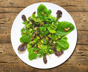 colorful salad of fresh spinach,onion sauce,old wood