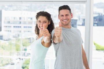 Couple gesturing thumbs up in bright exercise room
