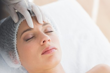 Woman recieving botox injection in forehead