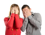Couple covering their eyes over white background