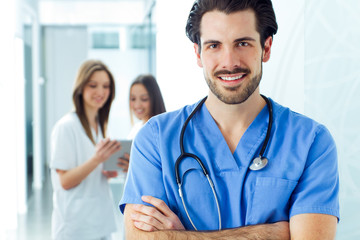 Cheerful young doctor leading his team