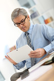 Senior businessman in office working on tablet