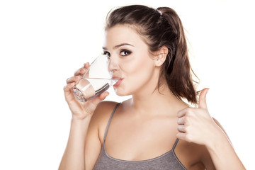 beautiful woman drinks water from a glass and showing thumbs up
