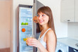 Young brunette girl with a glass of juice near the refrigerator
