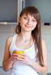 Young brunette girl with a glass of juice in the kitchen
