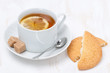 black tea with lemon and cookies on white wooden table