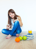 Young girl with headphones and green apple listening music at ho