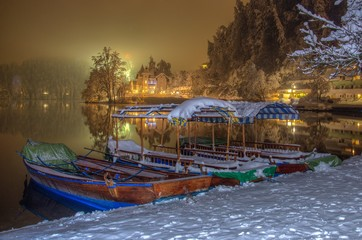 Pletna boats on the bank of Lake Bled in Winter snowy night