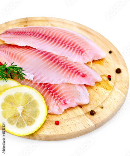 Fillets tilapia with lemon and dill on a board