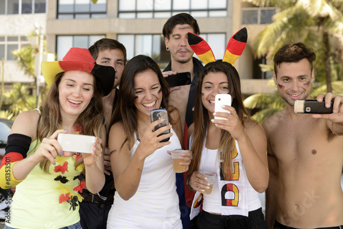 Group of happy German soccer fans holding smartphones