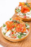 sandwich with cottage cheese, tomato and salmon on wooden board