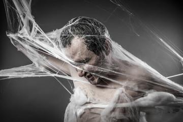 Spiderweb.man tangled in huge white spider web