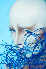 Attractive bald woman with body art on blue background